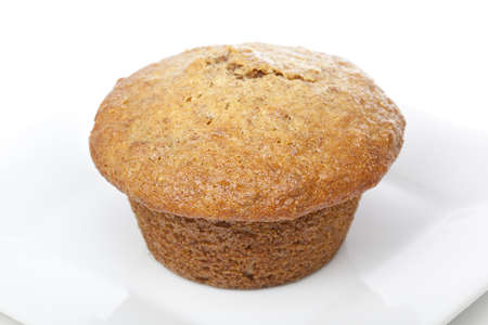 A fresh bran muffin against a white background