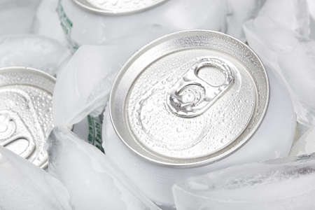 A group of soda cans in a container of ice photo