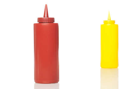 squirting ketchup: A mustard and ketchup bottle against a white background