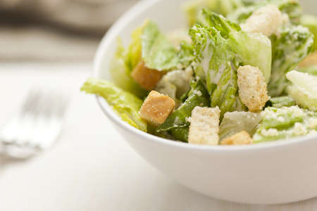 salad fork: Fresh green Caeser Salad with croutons and cheese