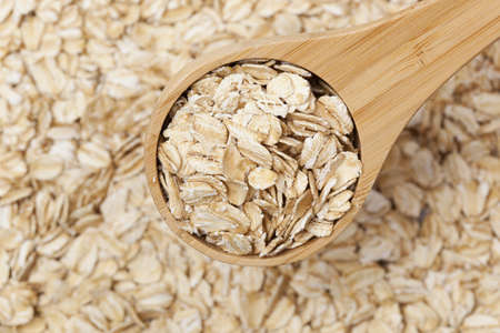 A Healthy Dry Oat meal in a wooden spoon photo