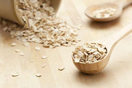 avena en hojuelas: Una comida saludable de avena seca en una cuchara de madera