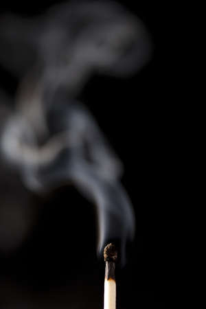 Burnt Wooden Matches smoking against a black background