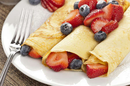 Fresh Homemade Rolled Strawberry Crepes with blueberries photo