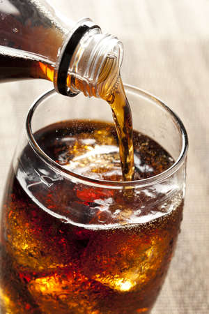 Refreshing Brown Soda with Ice on a background