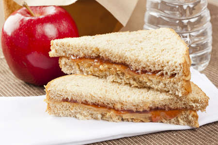 Peanut Butter and Jelly Sack Lunch with water and apple photo