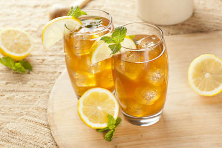 Refreshing Iced Tea with Lemon against a background Imagens