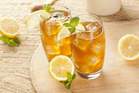 té helado: Té refrescante helado con limón sobre un fondo