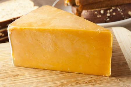 cheddar cheese: Traditional Yellow Cheddar Cheese on a background