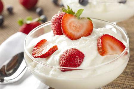 yaourts: Frais Yogourt biologique grec avec des fraises sur un fond Banque d'images