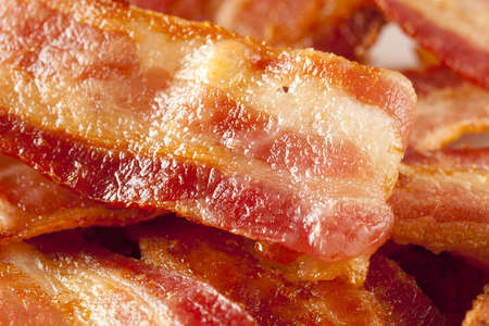 bacon fat: Cooked Greasy Bacon against a back ground