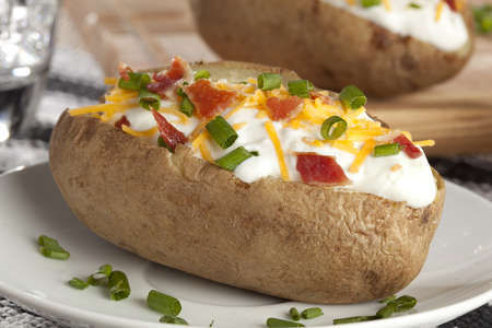 baked potato: Hot Baked Potato with chives, cheese, and sour cream Stock Photo