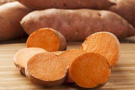 Fresh Organic Orange Sweet Potato against a background Stock Photo