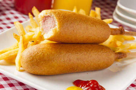 catsup: Organic CornDog on a stick with ketchup and mustard