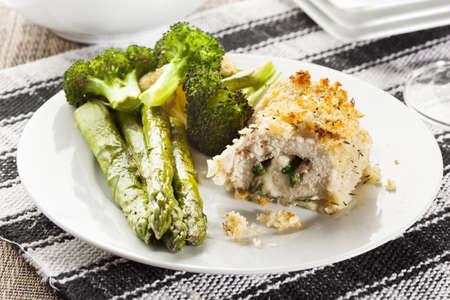 Breaded Homemade Chicken Cordon Bleu with fresh vegetables Banco de Imagens