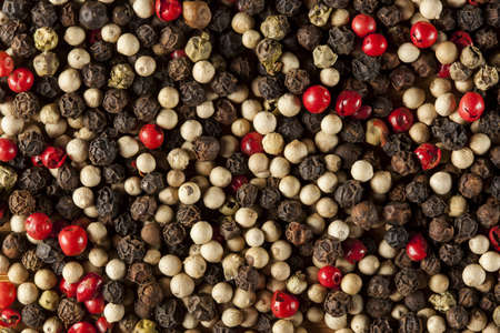 Raw Whole Four Peppercorn Blend against a background photo