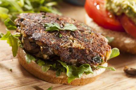 vegetarian hamburger: Homemade Organic Vegetarian Mushroom Burger with tomato and guacamole Stock Photo