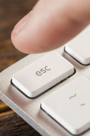 esc: Finger Pressing Escape on a white and Grey Computer Keyboard Stock Photo