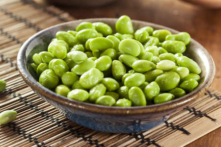 Cooked Green Organic Edamame with sea salt against a background photo