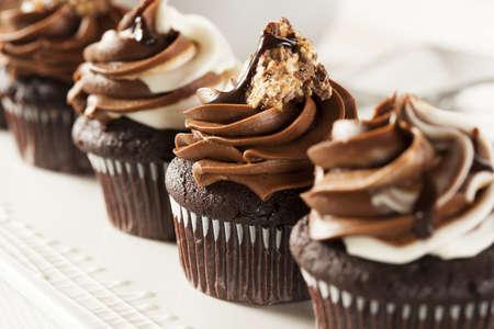 케이크: 배경에 초콜릿 설탕을 입 힘 제 초콜릿 컵 케이크