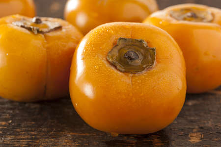 jhy: Organic Orange Persimmon Fruit against a background Stock Photo