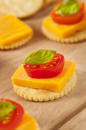 galletas integrales: Queso Cheddar y Cracker aperitivo con tomate y albahaca Foto de archivo