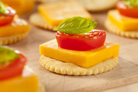 sliced cheese: Chedder Cheese and Cracker Appetizer with tomato and basil