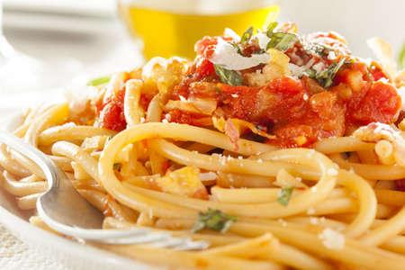 spaghetti: Zelfgemaakte Bucatini Amatriciana Pasta met saus en basilicum