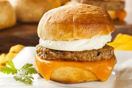 huevos revueltos: Sandwich de huevo casero con jam?n y queso en un rollo Foto de archivo