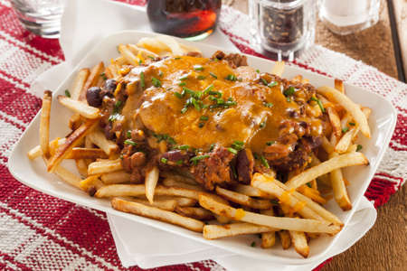 chili sauce: Unhealthy Messy Chili Cheese Fries on a Background Stock Photo