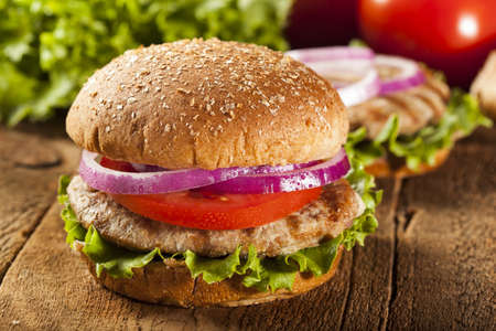 chicken burger: Homemade Turkey Burger on a Bun with Lettuce and Tomato Stock Photo