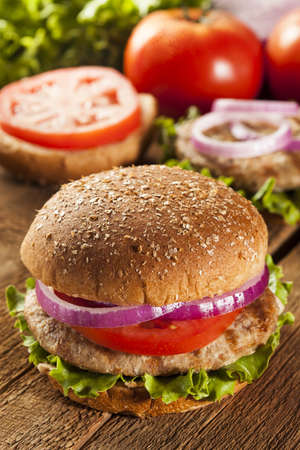 burger on bun: Homemade Turkey Burger on a Bun with Lettuce and Tomato Stock Photo