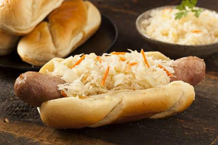 bratwurst: Homemade Bratwurst with Sauerkraut on a Roll Stock Photo