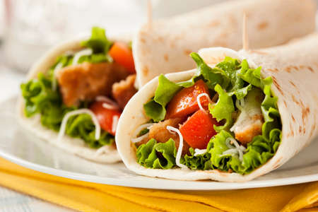 Breaded Chicken in a Tortilla Wrap with Lettuce and Tomato Stock Photo