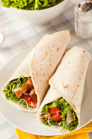 Breaded Chicken in a Tortilla Wrap with Lettuce and Tomato photo
