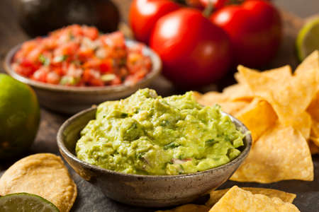 Green Homemade Guacamole with Tortilla Chips and Salsa