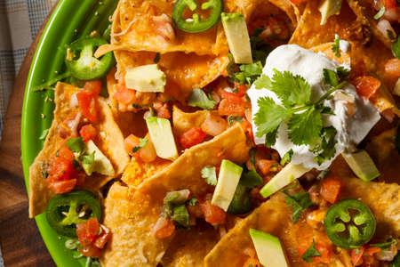 food an drink: Homemade Unhealthy Nachos with Cheese, Sour Cream, and Vegetables