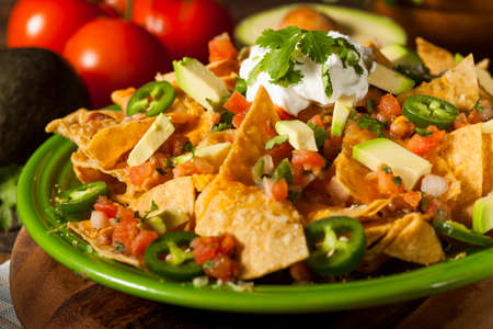 mexican: Homemade Unhealthy Nachos with Cheese, Sour Cream, and Vegetables