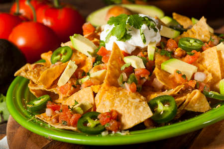 Homemade Unhealthy Nachos with Cheese, Sour Cream, and Vegetables