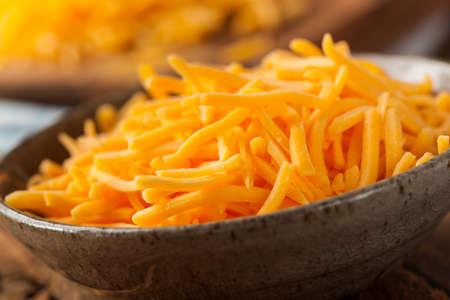 queso rallado: Orgánica queso rallado cheddar normal en una tabla de cortar Foto de archivo