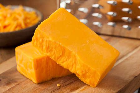 queso rallado: Orgánico Queso Cheddar Fuerte en una tabla de cortar Foto de archivo