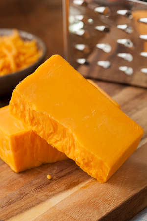 grated cheese: Organic Sharp Cheddar Cheese on a Cutting Board