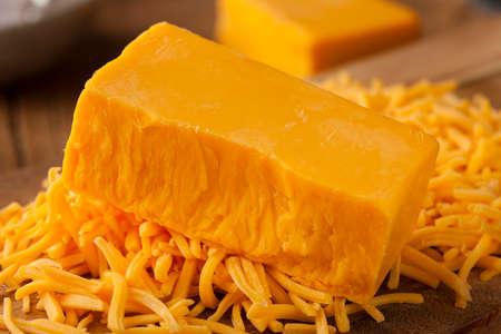 queso cheddar: Org�nico Queso Cheddar Fuerte en una tabla de cortar Foto de archivo