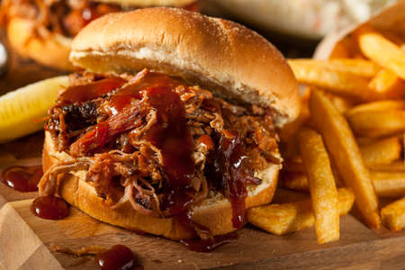 Barbeque Pulled Pork Sandwich with BBQ Sauce and Fries Stock Photo