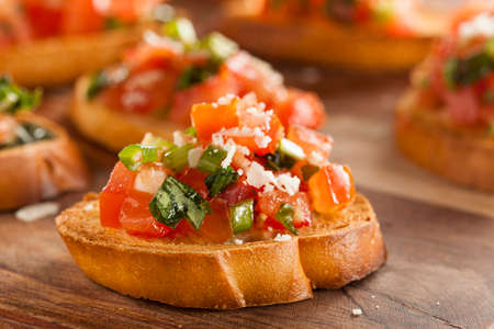 Homemade Italian Bruschetta Appetizer with Basil and Tomatoes Imagens