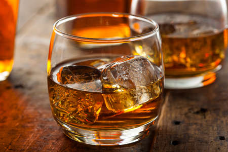 old bar: Alcoholic Amber Whiskey Bourbon in a Glass with Ice