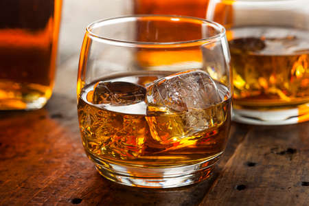 bourbon: Alcoholic Amber Whiskey Bourbon in a Glass with Ice