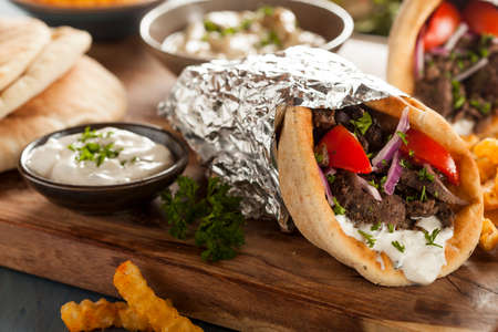 tzatziki: Zelfgemaakte Vlees Gyro met Tzatziki saus, tomaten en frieten Stockfoto