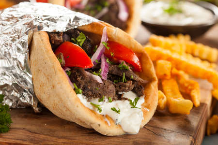 Homemade Meat Gyro with Tzatziki Sauce, tomatos and French Fries photo