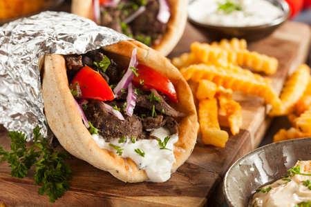 Zelfgemaakte Vlees Gyro met Tzatziki saus, tomaten en frieten Stockfoto